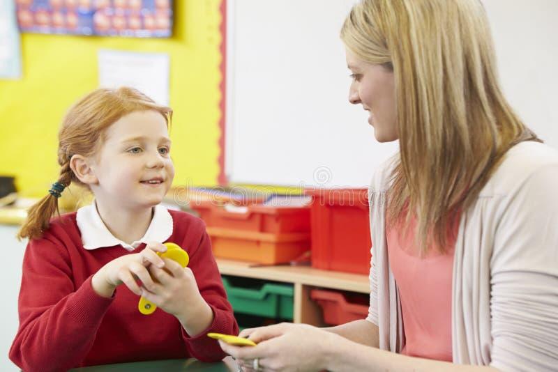 Lärare Helping Female Pupil med matematik på skrivbordet royaltyfria bilder