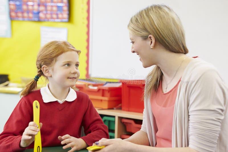 Lärare Helping Female Pupil med matematik på skrivbordet arkivfoto
