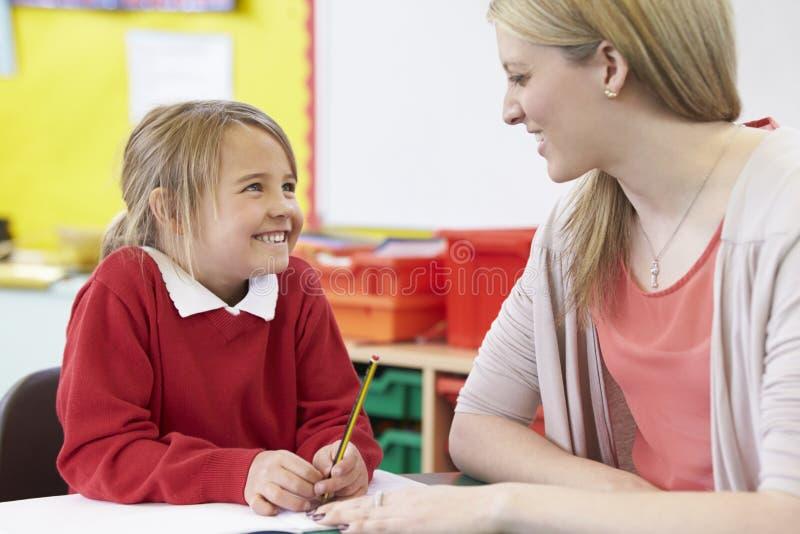Lärare Helping Female Pupil med praktiserande handstil på skrivbordet arkivfoto