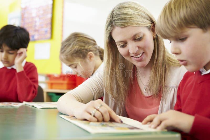 Lärare Helping Male Pupil med läsning på skrivbordet arkivfoton