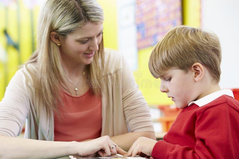 Lärare Helping Male Pupil med läsning på skrivbordet fotografering för bildbyråer