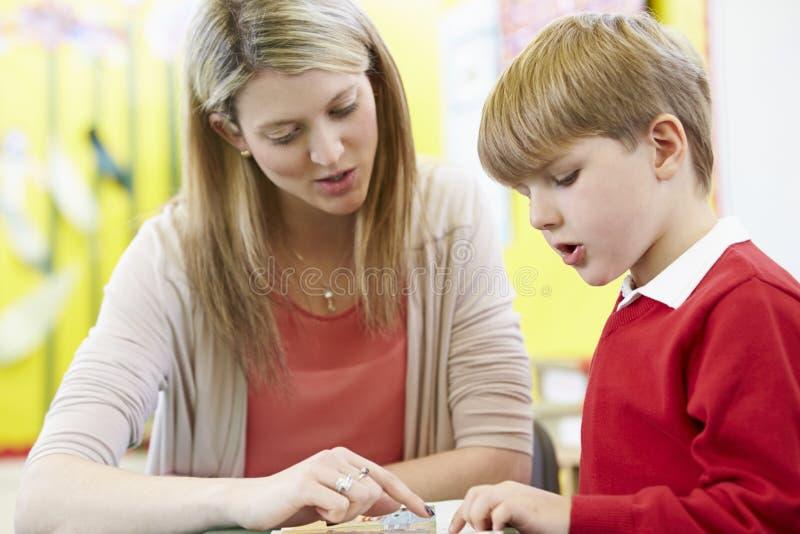 Lärare Helping Male Pupil med läsning på skrivbordet arkivbilder