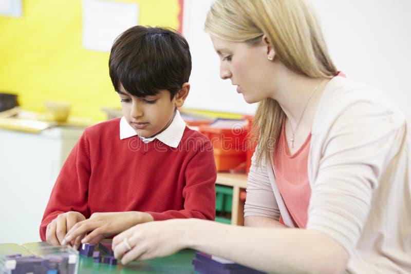 Lärare Helping Male Pupil med matematik på skrivbordet arkivbilder