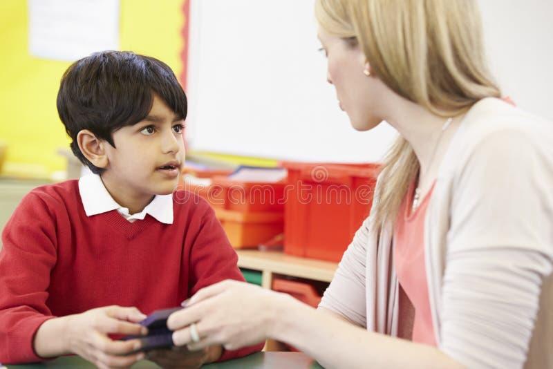 Lärare Helping Male Pupil med matematik på skrivbordet arkivfoton