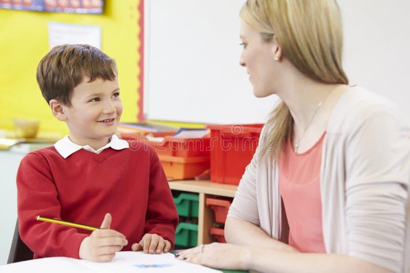 Lärare Helping Male Pupil med praktiserande handstil på skrivbordet arkivfoton