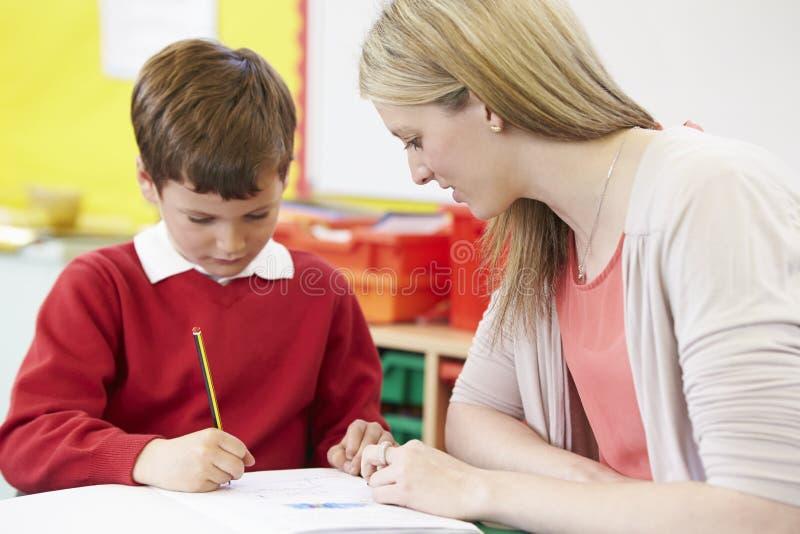 Lärare Helping Male Pupil med praktiserande handstil på skrivbordet royaltyfri foto