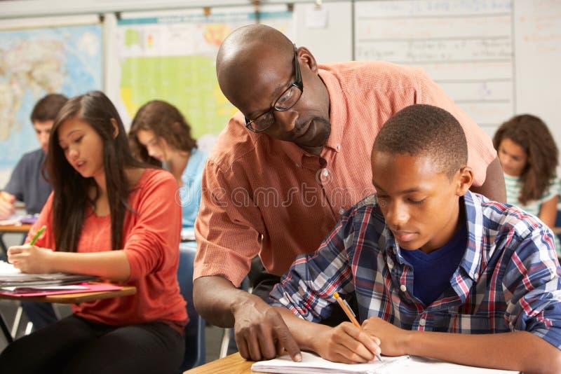 Lärare Helping Male Pupil som studerar på skrivbordet i klassrum royaltyfria foton