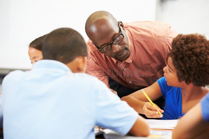 Lärare Helping Pupils Studying på skrivbord i klassrum arkivbilder