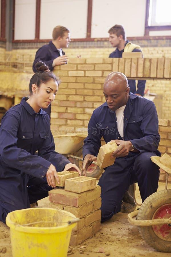 Lärare Helping Students Training som är byggmästare royaltyfri fotografi