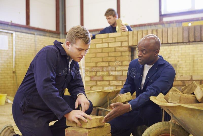 Lärare Helping Students Training som är byggmästare arkivbild