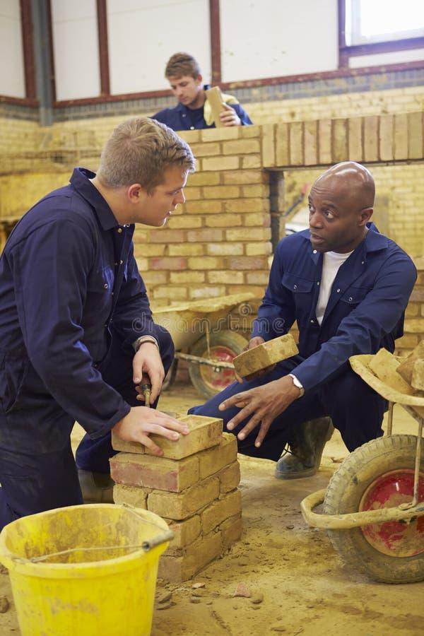 Lärare Helping Students Training som är byggmästare arkivbilder