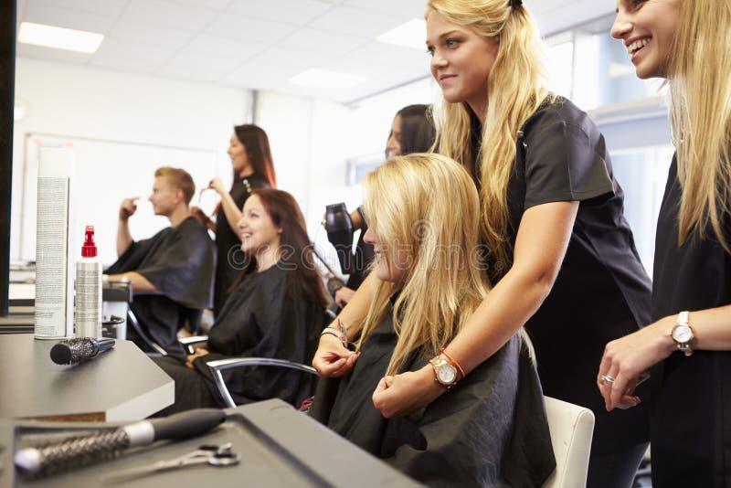 Lärare Helping Students Training som blir frisörer fotografering för bildbyråer