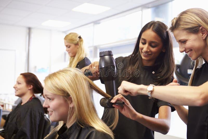Lärare Helping Students Training som blir frisörer arkivbild