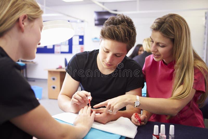 Lärare Helping Students Training som blir kosmetologer royaltyfri foto