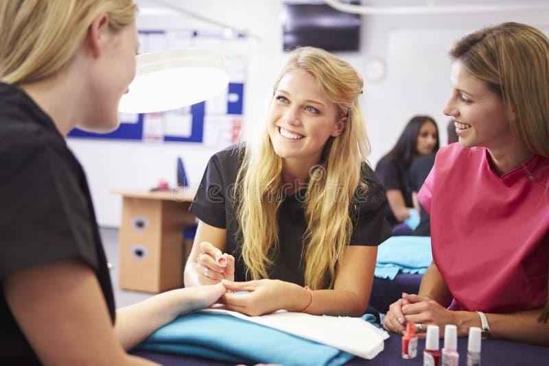 Lärare Helping Students Training som blir kosmetologer arkivbild
