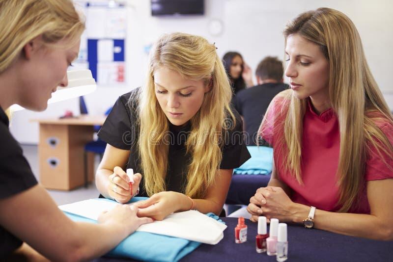 Lärare Helping Students Training som blir kosmetologer arkivfoto