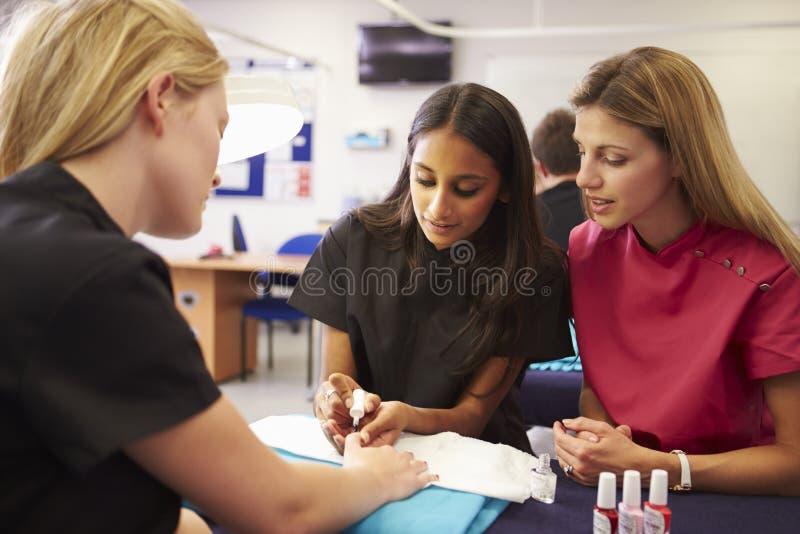 Lärare Helping Students Training som blir kosmetologer royaltyfri bild