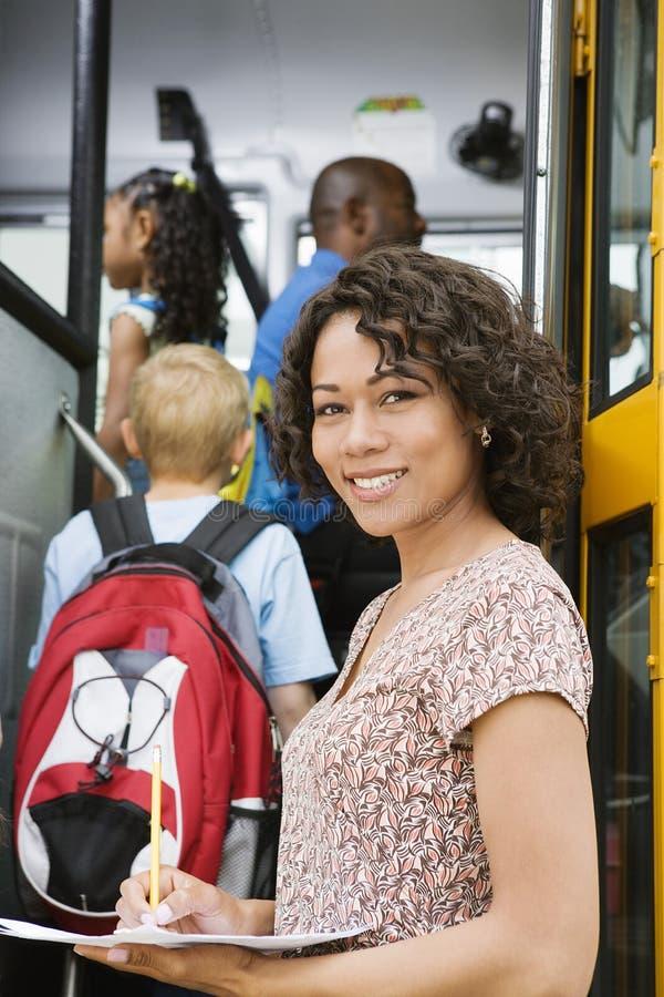 Lärare Loading Elementary Students på skolbussen arkivbilder