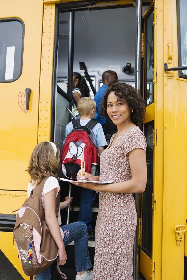 Lärare Loading Elementary Students på skolbussen fotografering för bildbyråer