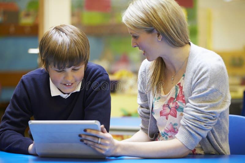 Lärare With Male Pupil som använder den Digital minnestavlan i klassrum fotografering för bildbyråer