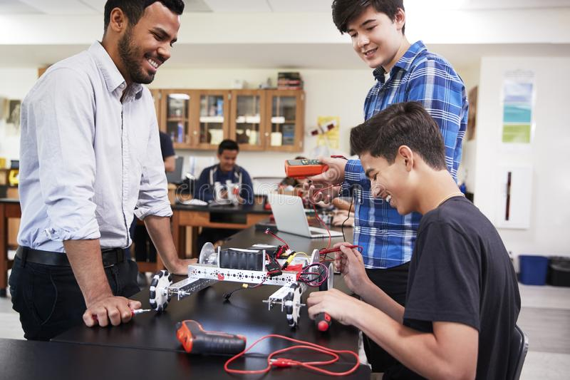 Lärare With Male Pupils som bygger det Robotic medlet i vetenskapskurs royaltyfri bild