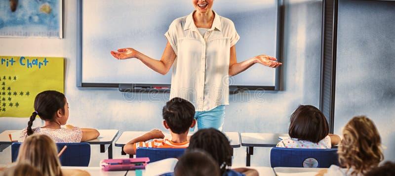 Lärare med armar som är utsträckta i klassrum royaltyfria foton