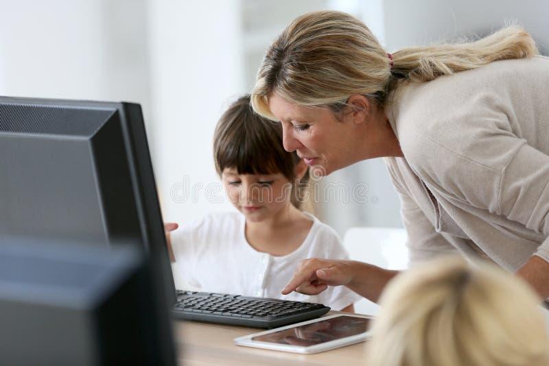 Lärare med barn på skolan genom att använda datoren royaltyfri bild
