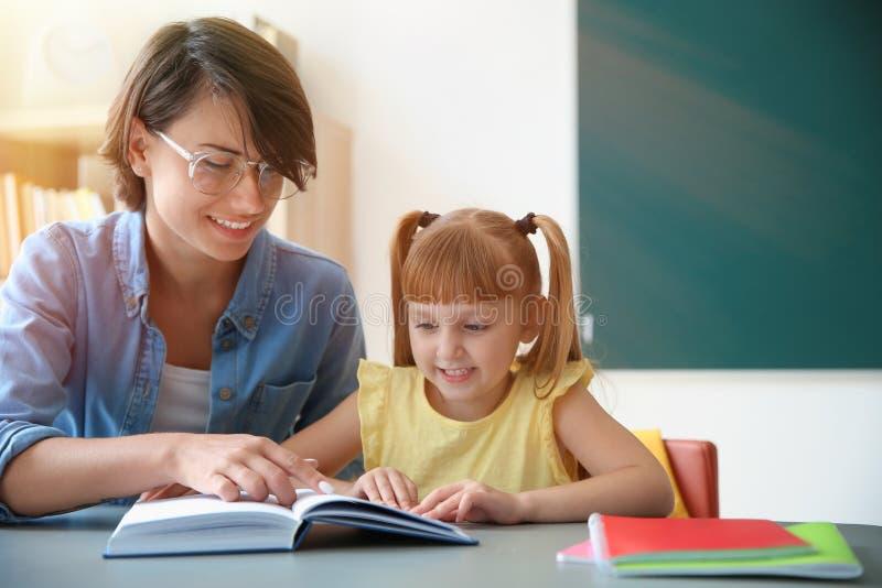 Lärare med elevläseboken på tabellen i klassrum royaltyfria foton