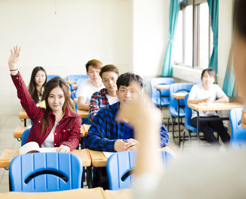 Lärare med gruppen av högskolestudenter i klassrum royaltyfri foto