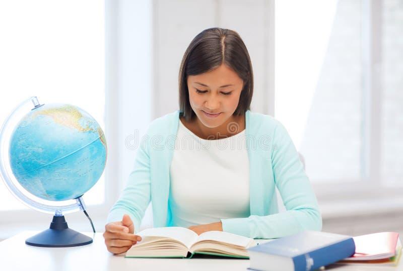 Lärare med jordklotet och boken på skolan arkivfoto