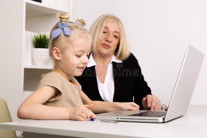 L?rare med lilla flickan som skriver p? b?rbara datorn i klassrumet arkivbild