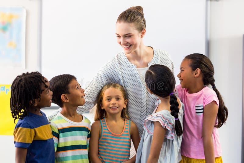 Lärare med skolbarn i klassrum royaltyfria bilder