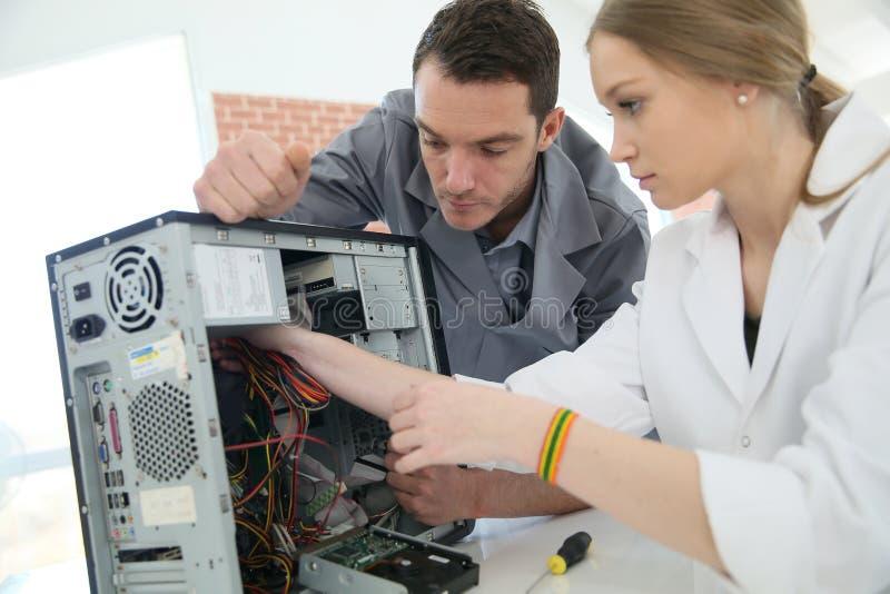 Lärare med studenten som reparerar datoren royaltyfri fotografi