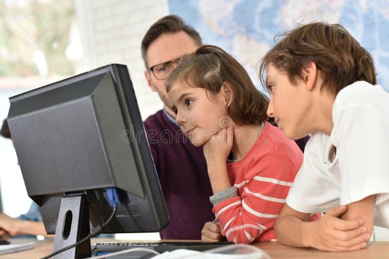 Lärare med ungar som är främsta av datoren royaltyfria bilder