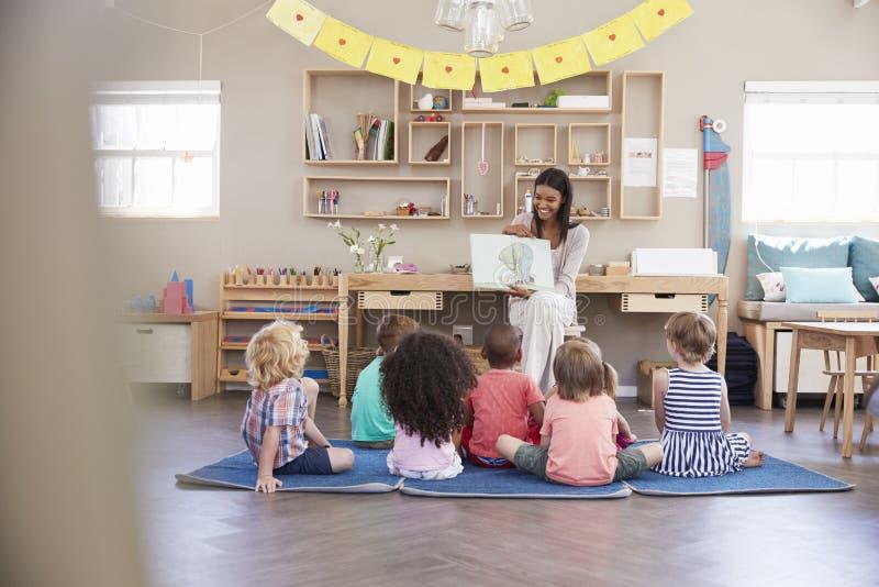 Lärare At Montessori School som läser till barn på berättelsen Tid fotografering för bildbyråer
