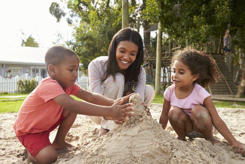 Lärare At Montessori School som spelar med barn i sandgrop royaltyfri foto
