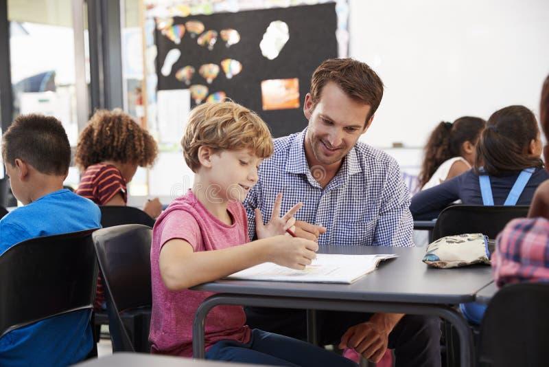 Lärare och barnskolapojke som ser anteckningsboken i grupp arkivfoton
