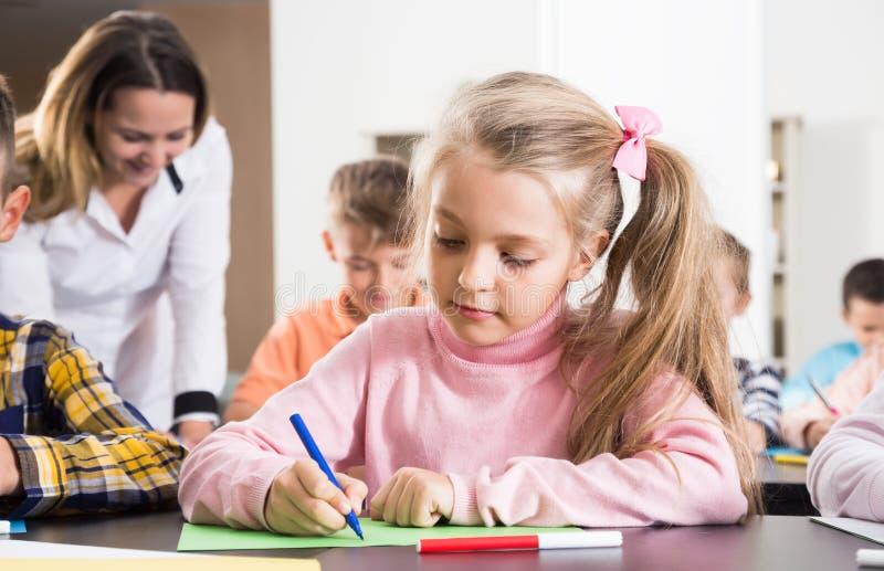 Lärare och elementära ålderbarn som drar på klassrumet arkivfoton