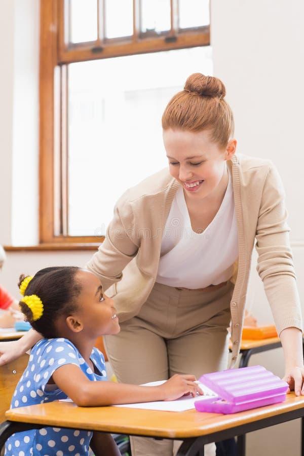 Lärare och elev som tillsammans arbetar på skrivbordet royaltyfri fotografi
