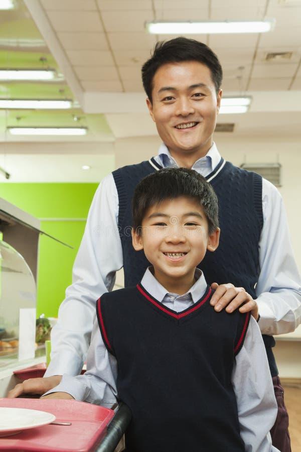 Lärare- och för skolapojke stående i skolakafeteria arkivbild