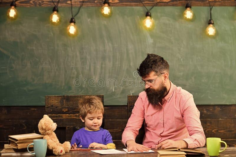 Lärare och liten unge som tillsammans drar Visningpojke för manlig lärare hur man skisserar handen på papper Individuell utbildni fotografering för bildbyråer