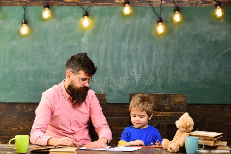 Lärare och liten unge som tillsammans drar Visningpojke för manlig lärare hur man skisserar handen på papper Individuell utbildni arkivbild