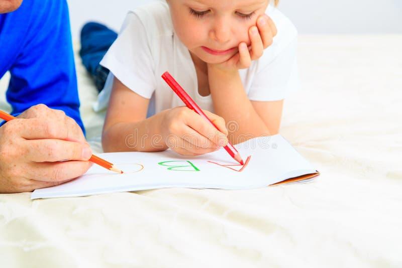 Lärare och litet barn som lär att skriva brev fotografering för bildbyråer