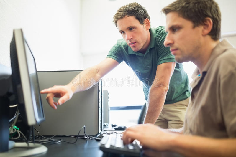 Lärare och mogen student i datasal arkivbild