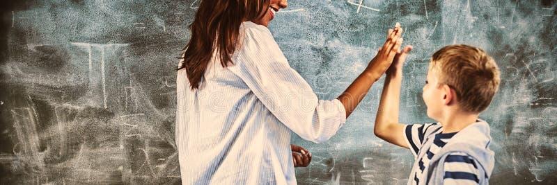 Lärare och pojke som ger högt fem i klassrum arkivbilder