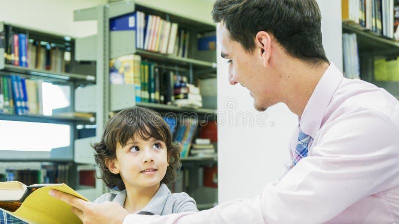 lärare- och pojkestudenten lär med boken med bokhyllabackgroun royaltyfri foto