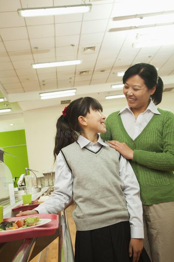 Lärare- och skolaflickastående i skolakafeteria royaltyfria bilder