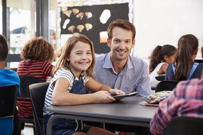 Lärare och skolflicka som använder minnestavlan i gruppblick till kameran royaltyfri foto
