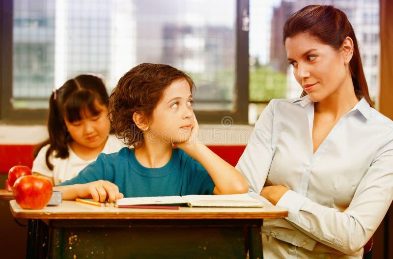 Lärare och skolpojke som ser sig i primärt klassrum arkivfoton