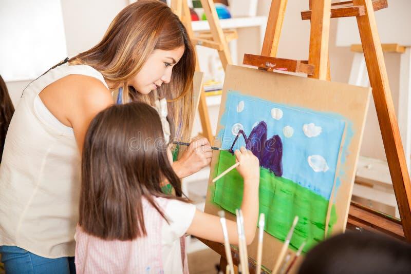 Lärare och student som tillsammans målar royaltyfri bild